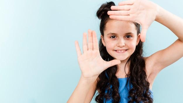 Милая девушка делает форму камеры с руками