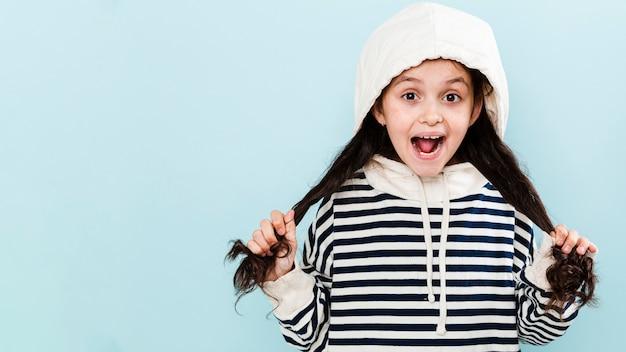 Милая девушка с капюшоном играет с волосами