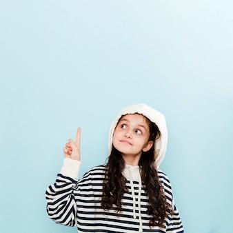 Маленькая девочка с капюшоном, указывая выше