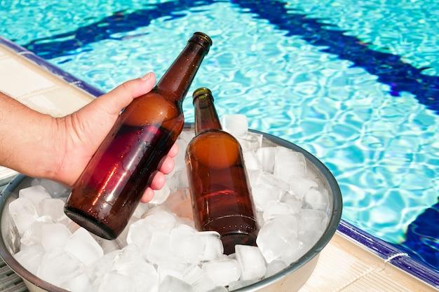Рука вынимает бутылку пива из лотка со льдом