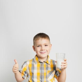 ミルクのガラスを手で保持している少年