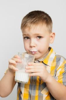 ガラスからミルクを飲む少年