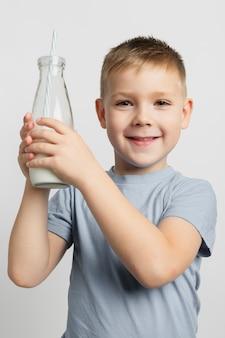 ストローで牛乳瓶を保持している若い男の子