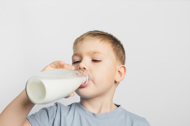 Мальчик пьет молоко с бутылкой