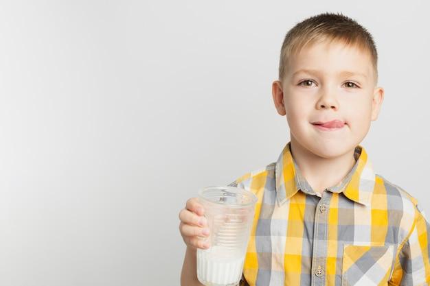 ミルクのガラスを保持している若い男の子