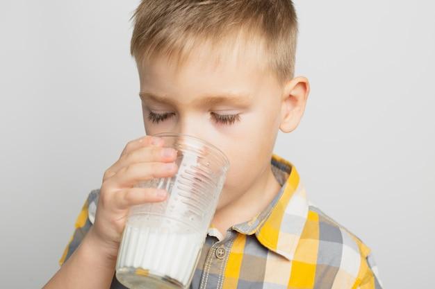 Малыш пьет молоко со стаканом