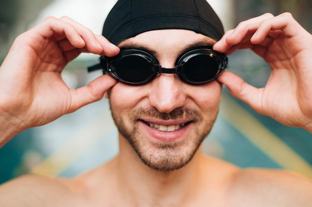 水泳ゴーグルを配置するスマイリーの男性