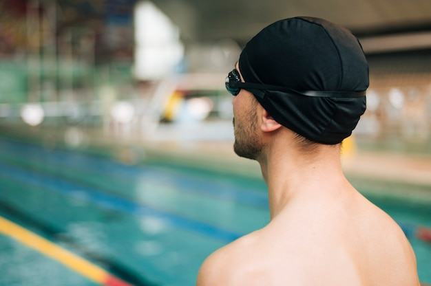 スイミングプールでサイドビュー若い男性