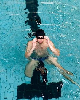 水泳ゴーグルを配置する高角度の男性