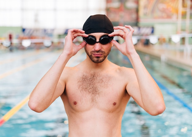 スイミングゴーグルを置く若い男の正面図