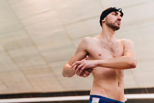 水泳の練習の前にストレッチの若い男性