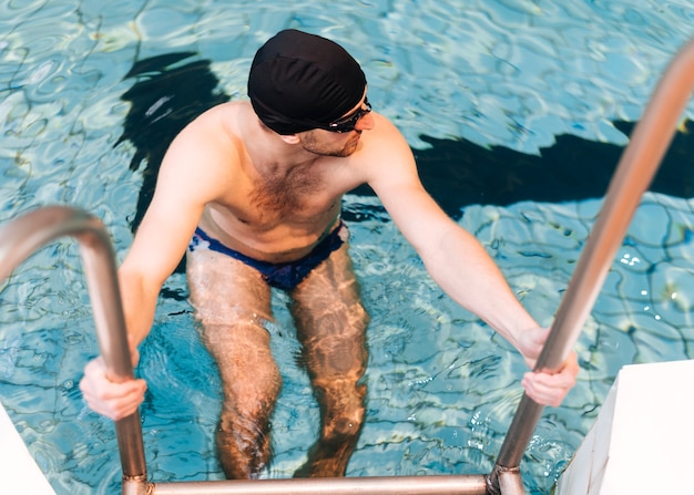 プールから出て高角度の若いスイマー