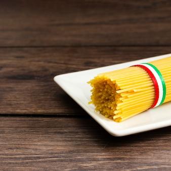 Спагетти на тарелке с деревянным хлебом