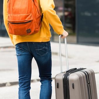 荷物を持つ一人の旅行者の背面図