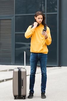 彼の携帯電話をチェックするハンサムな若い旅行者