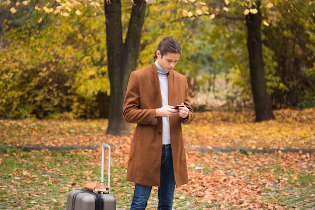若い男が公園で彼の携帯電話をチェック