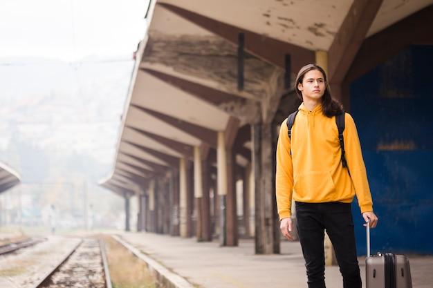 Стильный молодой человек ждет поезд