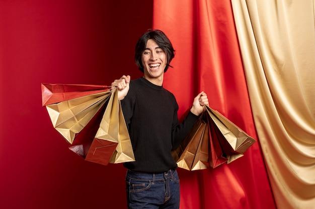 Улыбающийся человек позирует с сумками для китайского нового года