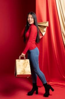 中国の新年の紙の買い物袋でポーズカジュアルな女性