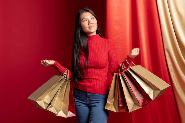 中国の新年の買い物袋を保持しているカジュアルな服装の女性
