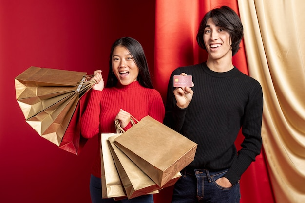 中国の新年のバッグでポーズをとってスマイリーカップル