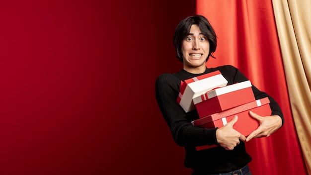 Мужчина держит коробки на китайский новый год