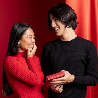 Мужчина предлагает подарок женщине на китайский новый год