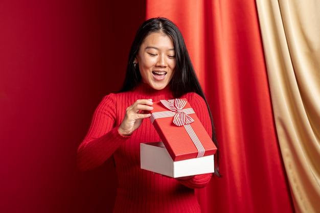中国の新年のギフトボックスを開く女性