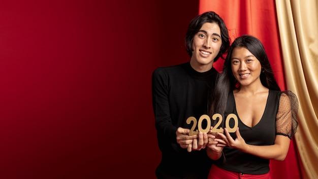 新年を保持しているカップルがコピースペースで署名します。