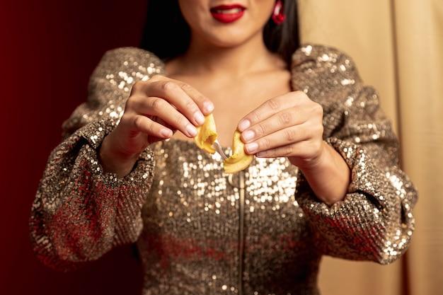 中国の新年のフォーチュンクッキーを引き裂く女性