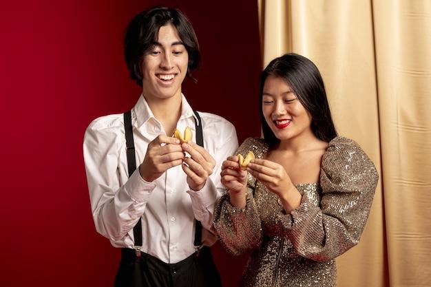 中国の新年のフォーチュンクッキーからのメッセージを読んで幸せなカップル