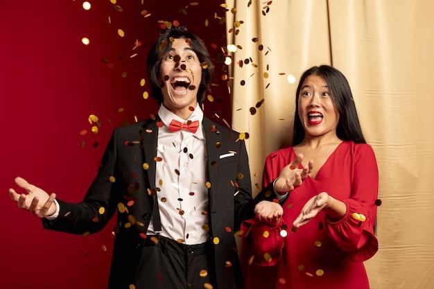 黄金の紙吹雪を投げて楽しんでいるカップル