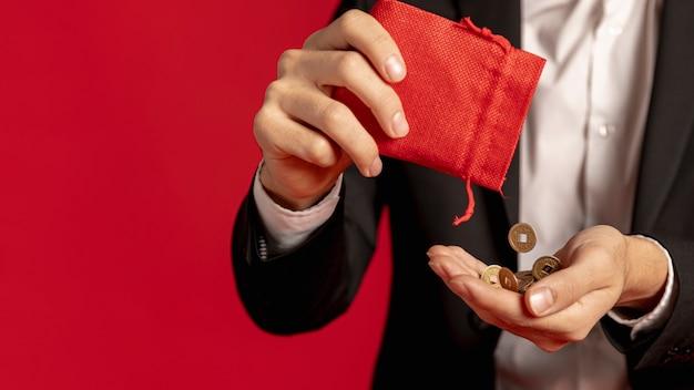 Мужчина держит золотые монеты с красной сумкой на китайский новый год