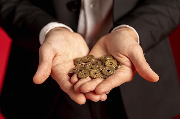 Мужчина держит золотые китайские монеты в руках на китайский новый год