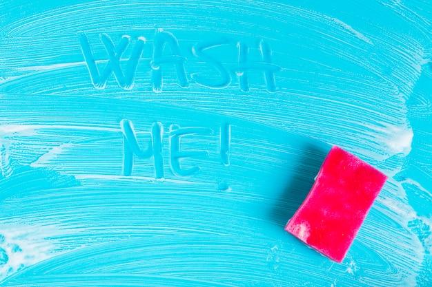 トップビューの石鹸の泡と青色の背景にスポンジ