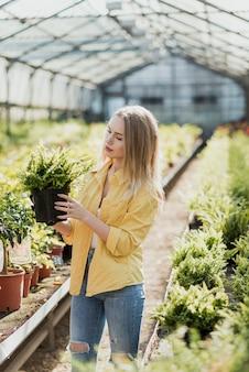 植物とポットを保持している高角度の女性