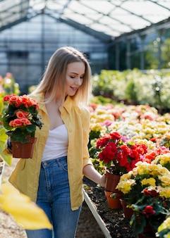 Женщина в теплице ухаживает за цветами