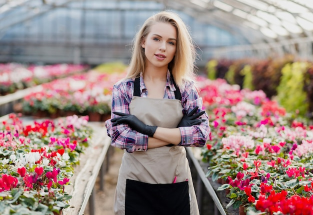花の世話をするエプロンを持つフロントビュー女性