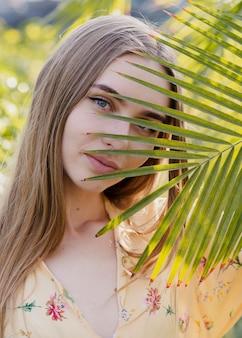 植物の葉を通して見るクローズアップ女性