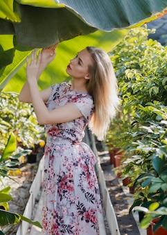 温室ポーズで花柄のドレスを持つ女性