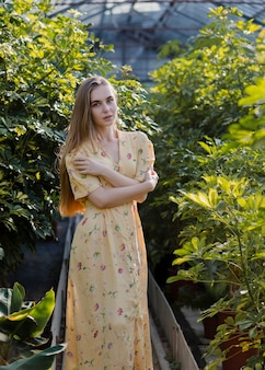 Женщина в длинном летнем платье позирует в теплице