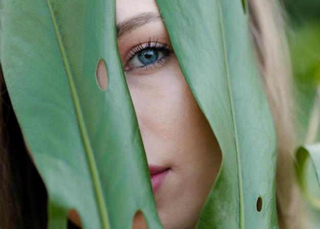 Крупным планом девушки смотрят сквозь листья