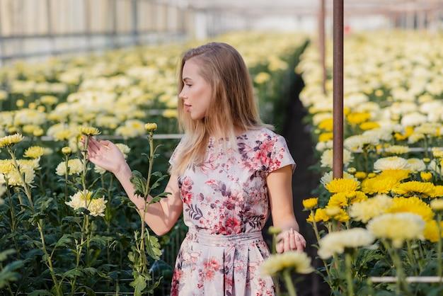 温室の花のドレスを持つ女性