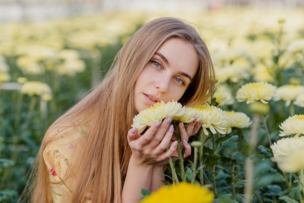 花が付いている温室の若い女性
