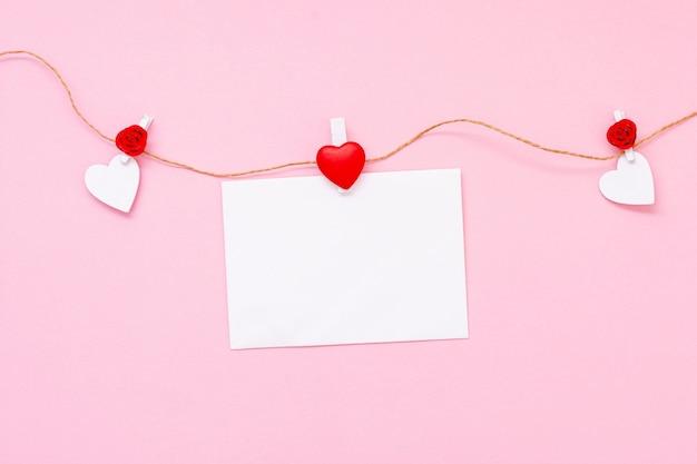 Композиция сверху с сердечками и листком бумаги