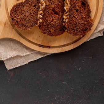 Нарезанный хлеб на деревянном фоне с тканью