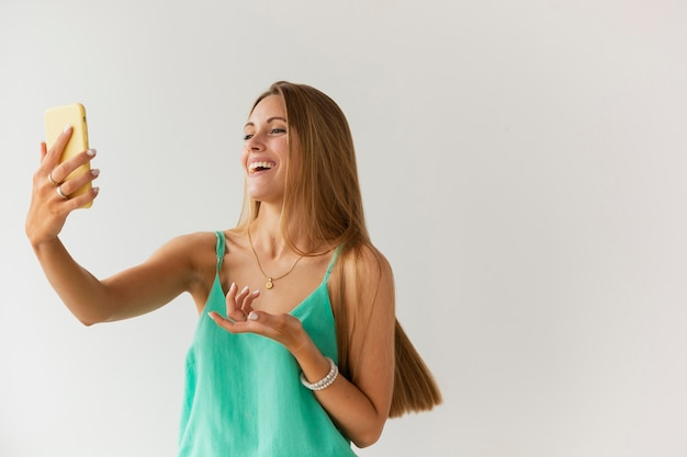 Низкий угол смайлик женщина берет селфи