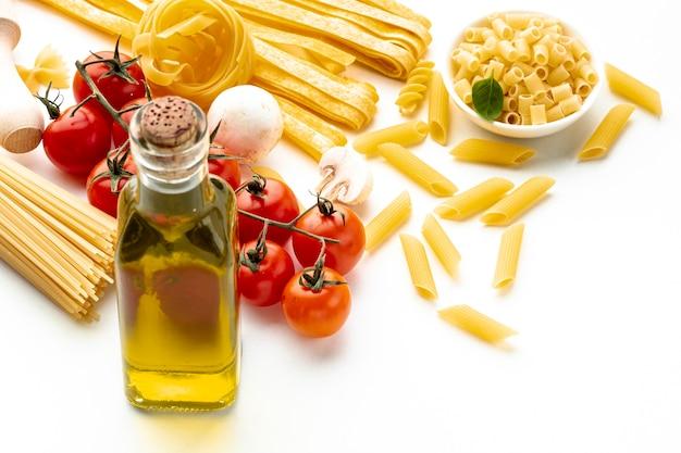 Сырые макароны под большим углом с помидорами и оливковым маслом