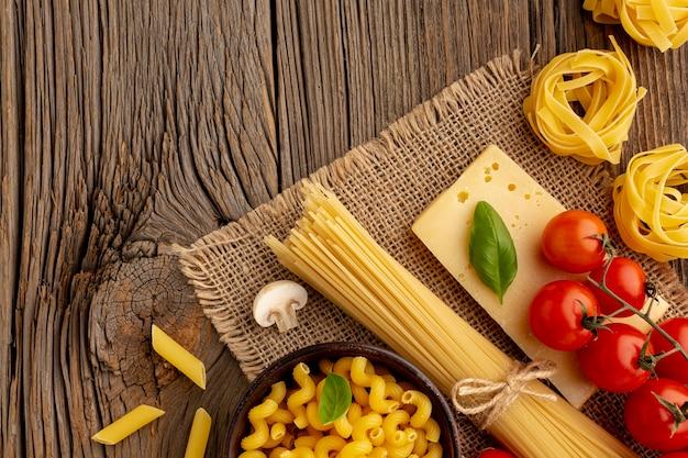 Сырые спагетти целлентани пенне помидоры и твердый сыр