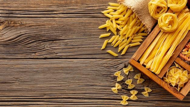 Сырые макаронные изделия в деревянной коробке на столе